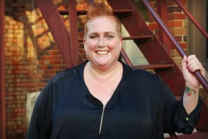 Author photo of Avery Guess, a woman with red hair pulled back away from her face, wearing a dark blue zip up shirt with a colorful wrist tattoo, standing in front of a red fire escape and a brick building.