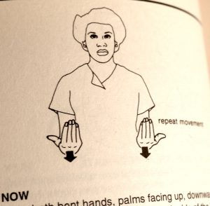 "A drawing of a person signing with their palms facing up and arrows pointing down. A description says ""repeat movement"" next to it, and the words ""Now,"" ""hands,"" ""palms facing up,"" on the bottom, with other words obscured or cut off"