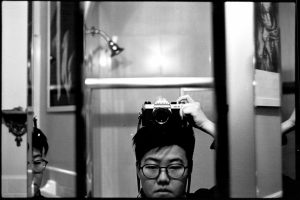 A black-and-white photograph of Yanyi, who has short dark hair and is wearing glasses. Yanyi is steadying his SLR camera on the top of his, taking the photograph in bathroom mirror. The mirror is triple beveled, a fragment of his face visible in the leftmost section, and a fragment of his wrist is visible in the segment to the right.
