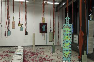 Wide angle photograph of the Conclusions and Findings exhibition space. Numerous decorated paddles bearing poems hang from the ceiling on red ribbons by the handles. The floor below them is scattered with petals.