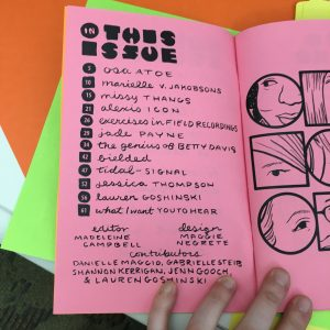 Photograph of the table of contents of an issue of Women in Sound Zine, pink paper with black writing on the left page and black ink illustrations of faces on the right page.
