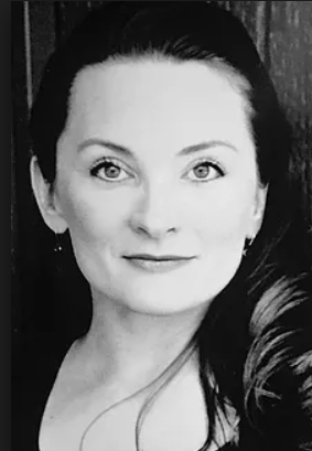 A black and white photograph of reviewer Jody T Morse, a woman with long dark hair and light eyes. She's looking into the camera with a slight smile, and one eyebrow subtly raised.