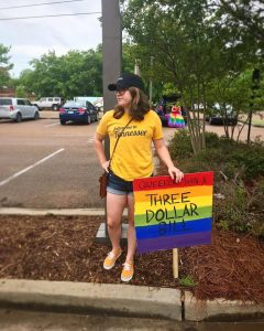 "A full body photograph of the author, Jennie Frost. They are standing on a street median holding a rainbow-painted sign reading ""Queerer then a three dollar bill."" They're wearing a yellow shirt and jean shorts, and have shoulder-length light brown hair loose under a black baseball cap. With their hand on their hip, they're looking off into the distance, or possibly away from the camera."