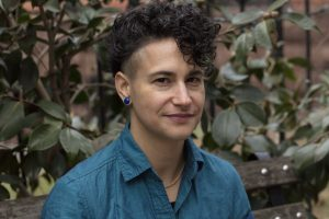 A photo of the author, Yana Calou, a Brazilian-American organizer and writer. They have curly dark hair that's shaved on the sides, curls cascading down their forehead. Their nose piercings are subtle, contrasted with their commanding blue round earrings match their blue button-down shirt, exposing a glimpse of a gold chain. They're sitting on a bench in front of thick-leaved creeping plants, they're smiling slightly, with a knowing look, and a smile in their eyes.