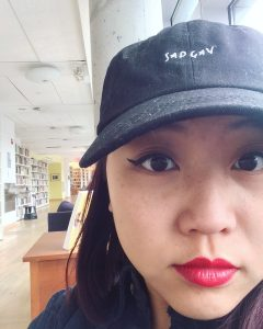 A photo of the author, Jody Chan, a person with shoulder-length hair and a baseball cap, wearing red lipstick.