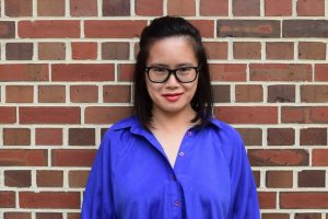 A woman standing in front of a brick wall, wearing a blue button up shirt.