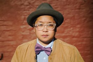 A photo of the author, a brown round queer person with glasses smiles and wears a purple bow tie & fedora against a red brick wall background.