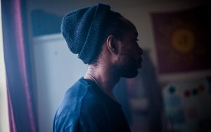 photo of author wearing a dark beanie standing in a profile pose.