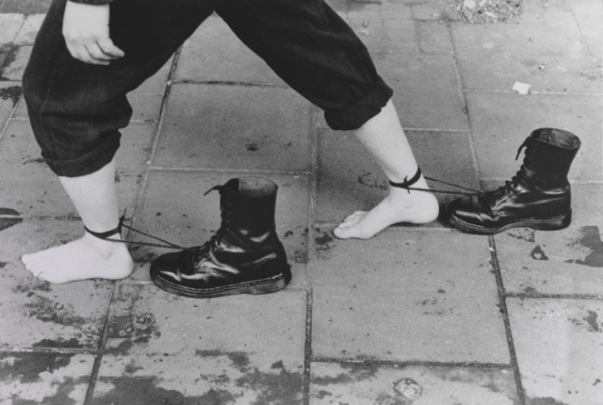 A black and white photograph of a person of unknown gender and race walking on a stone walkway with combat boots laced around their ankles, dragging behind them.