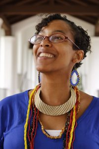 A photo of the author, Raina J. León, an African-American woman with short dark hair, glasses, beaded earrings, and an ensemble of necklaces over a blue blouse. She is looking upward and smiling.