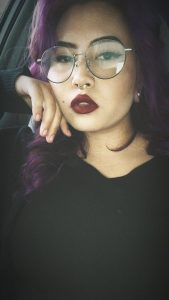 A photo of the author, a person with large glasses and purple hair, wearing lipstick and a black shirt,