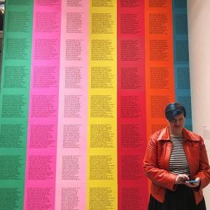 "Sarah Nichols, a white woman with blue hair wears a red faux leather jacket over a black and white horizontal striped shirt. She is standing in front of artist Jenny Holzer's ""Inflammatory Essays,"" text printed on 7 colors of paper arranged in columns, creating a rainbow. The text cannot be read clearly."
