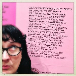 "A photo of Cathleen Allyn Conway, a white woman with long black hair and light eyes. Half of her face is out of frame as she looks up playfully through her black-framed cat-eye glasses at one of Jenny Holzer's ""Inflammatory Essays."" Printed on pink paper, part of Holzer's piece reads, in all capital letters: ""Don't talk down to me. Don't be polite to me. Don't try to make me feel nice. Don't relax. I'll cut the smile off your face. You think I don't know what's going on. You think I'm afraid to react. The joke's on you. I'm biding my time, looking for the spot. You think no one can reach you. No one can have what you have. I've been planning while you're playing. I've been saving while you're spending. The game is almost over so it's time you acknowledge me. Do you want to fall not ever knowing who took you?"