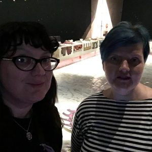 A photo of two women at a party. The woman on the left is Cathleen Allyn Conway, a dark-haired woman with cat-eye glasses and a big smile. Sarah Nichols stands to her right, with short blue hair and a black and white horizontal striped shirt.